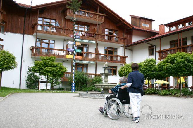 Innenhof mit Rollstuhlfahrer und Pflegekraft Pflege- und Therapiezentrum Bayerisch Gmain